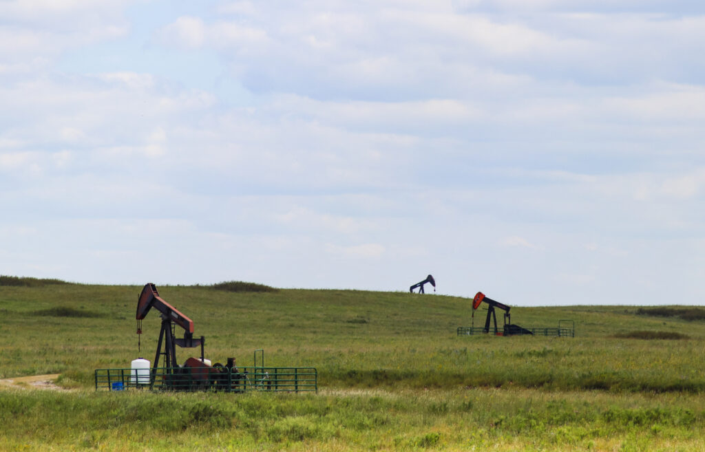 Three working pump jacks on oil or gas wells out in a green field