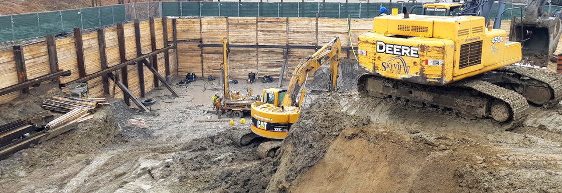 TRAK drill rig operators making geoexchange boreholes in bottom of foundation excavation for 8Haus Boutique Condos